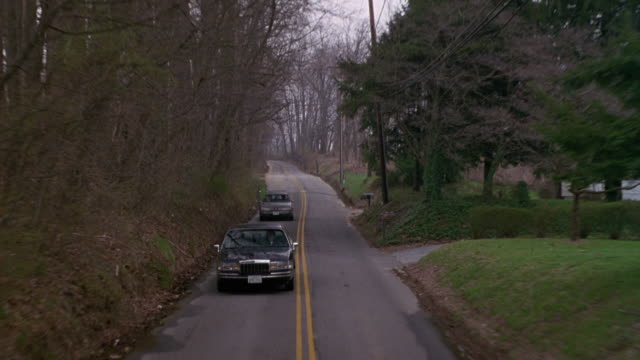 MEDIUM ANGLE MOVING POV OF BLACK LINCOLN TOWNCAR WITH BLACK FORD ESCORT IN BACKGROUND. LEAVES ON GROUND, PROBABLY LATE AUTUMN. COULD BE PART OF MOTORCADE, POSSIBLY GOVERNMENT ESCORT.
