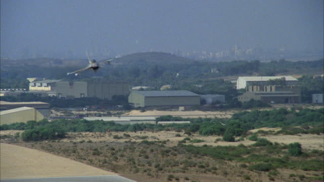 TRACKING SHOT OF A CAMOUFLAGE F-16 FIGHTER JET FLYING OVER RUNWAY AND DESERT PLAINS AREA. MIDDLE EAST.