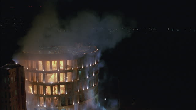 wide angle of multiple explosions from inside multi-story building with lights on outside. see coliseum-like architecture. could be office building, medical center, or high rise. - fire hose stock-videos und b-roll-filmmaterial