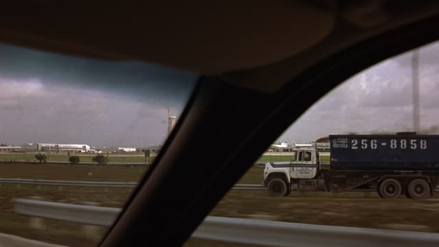 driving pov on highway from passenger side of vehicle. blue and white garbage dump truck merges almost right into pov.  airport in background. moderate traffic. office buildings on left. - garbage truck stock videos and b-roll footage