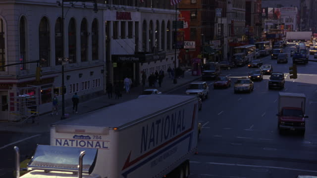 wide angle down of city street traffic on one-way street. see multi-story buildings framing either side of street. see yellow taxi cabs, passenger vehicles, national semi-truck, and empire cement truck drive towards pov. - anno 1999 video stock e b–roll