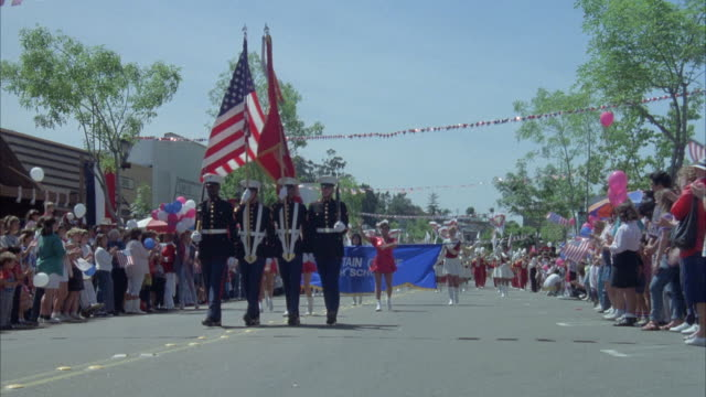 medium angle of memorial day celebration parade with marching bands, veterans, flag girls, floats and soldiers carrying flags. see crowds of people lining street waving flags and holding red, white and blue balloons. - military parade stock videos & royalty-free footage