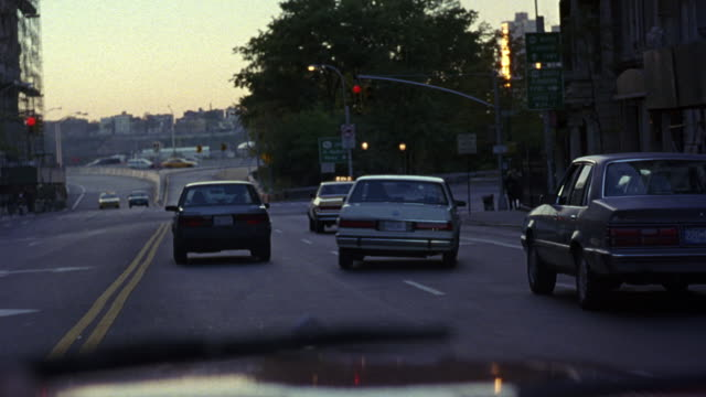 MEDIUM ANGLE OF WHITE 1987 BUICK LESABRE ON NEW YORK CITY STREET INTERSECTION. SEE CAR SWERVE ON ROAD AROUND CARS, CHANGE LANES, DRIVE ON WRONG SIDE OF DOUBLE YELLOW LINE,