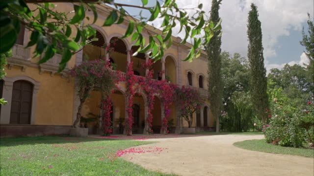 MEDIUM ANGLE OF OLD SPANISH VILLA OR HOUSE OR MANSION. SEE PEACH OR CREAM COLORED EXTERIOR WALLS AND ARCHED DOORWAY ARCHITECTURE. SEE HORSE-PULLED CARRIAGE OR BUGGY ARRIVE IN FRONT OF HOUSE ON DIRT PATH.