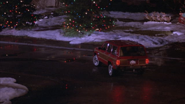 medium angle of red jeep cherokee leaving driveway and driving down middle class residential area or - Jeep Christmas Decorations