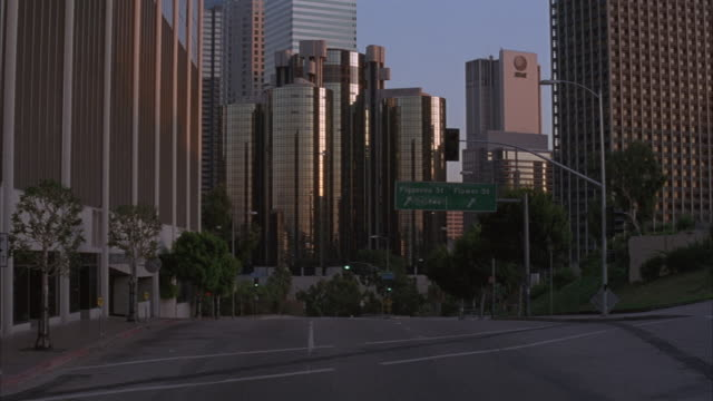 medium angle of city street in downtown area. see westin bonaventure hotel at end of street in background. see motorcade drive by from under and past pov towards bonaventure hotel. - 1993 stock-videos und b-roll-filmmaterial