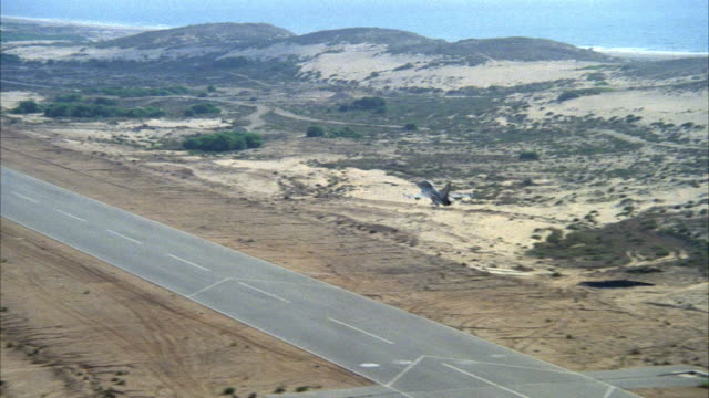TRACKING SHOT OF A CAMOUFLAGE F-16 FIGHTER JET FLYING OVER RUNWAY IN DESERT. SKY IS GRAY AND SMOGGY. MIDDLE EAST.