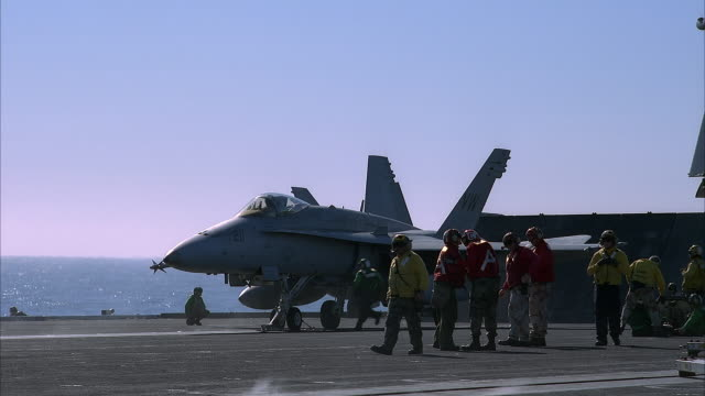medium angle of f/a-18 hornet on deck of u.s. navy ship, aircraft carrier. seamen, workers in yellow and red jackets wearing helmets on deck prepping the hornets for takeoff. - us navy stock videos and b-roll footage