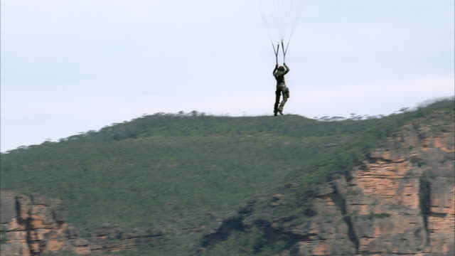 aerial view of stunt of person hanging in air from parachute-like device. instead of parachute see straps attach to metal wires which extend out of frame. could be man in military uniform. - 1989 stock videos and b-roll footage