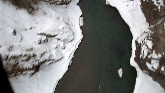 aerial birdseye pov of partially frozen river in snowy mountain gorge. could be ravine or valley. see snow on rocky terrain, ice, and open water. could be plate. winter. - frozen water stock videos & royalty-free footage