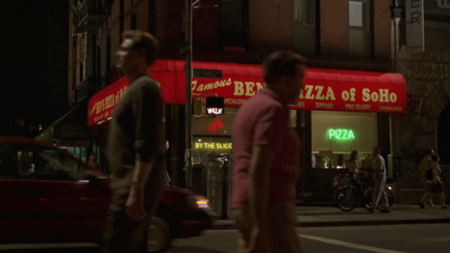 MEDIUM ANGLE OF CITY STREET CORNER WITH RED SIGN FOR FAMOUS BEN'S PIZZA OF SOHO PIZZERIA. SEE NEON SIGNS IN WINDOW ADVERTISING PIZZA AND BY THE SLICE.
