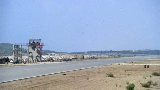 WIDE ANGLE OF MILITARY RUNWAY WITH CAMOUFLAGED CONTROL TOWER IN BACKGROUND. F-16 FIGHTER JET LANDS AND MOVES ACROSS RUNWAY TO LEFT. SEE SOLDIERS MOVING IN BACKGROUND NEAR CONTROL TOWER. MIDDLE EAST.