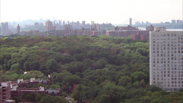 AERIAL OF LARGE WHITE BUILDING AMONG DENSE TREES. SEE NEW YORK CITY SKYLINE AND BRIDGE IN FAR DISTANCE. SEE SMALLER BRICK BUILDING TO LEFT OF WHITE BUILDING. PANS DOWN TO RESIDENTIAL AREA OR NEIGHBORHOOD. SEE FOUR LANE ROAD WITH CARS DRIVING.