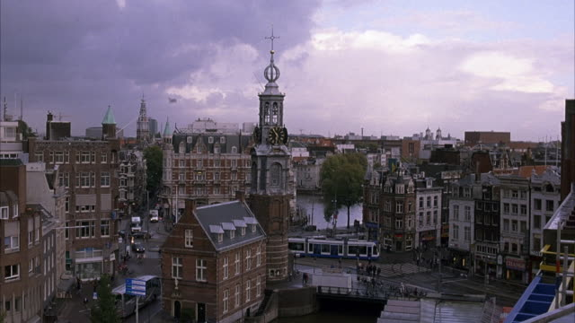 vídeos de stock e filmes b-roll de wide angle of clock tower in amsterdam during overcast day. streets look just rained on. cars and pedestrians on streets below. clock tower in middle of commercial center. see public transportation buses driving around. - torre de relógio