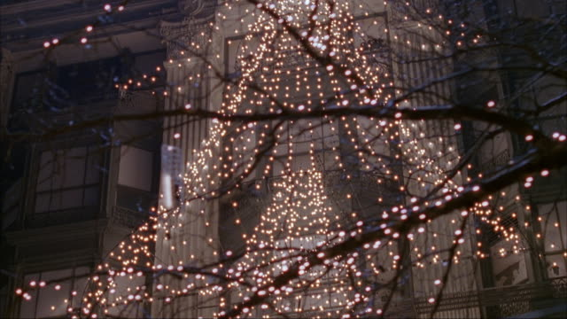 process plate of large angel made from strands of christmas lights on office or apartment building. pans down to street level to see entrance to macy's. see cars and taxis stopped in traffic. - fairy lights stock videos & royalty-free footage