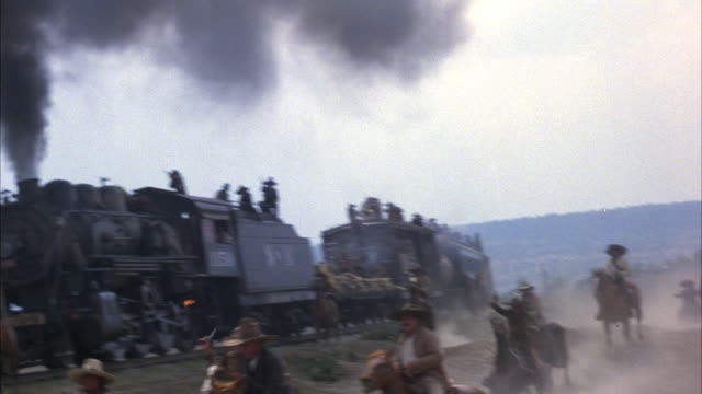 medium angle moving pov of steam engine train on left and mexican cowboys on horseback on right. see soldiers on roof of train shooting off into the distance over camera. - cowboy stock videos & royalty-free footage