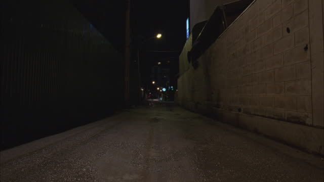 wide angle of people riding motorcycles toward camera down alley. see cars and vans drive past on street in background. downtown urban area. could be gang on dirt bikes. street lights. chases. - motorcycle biker stock videos & royalty-free footage