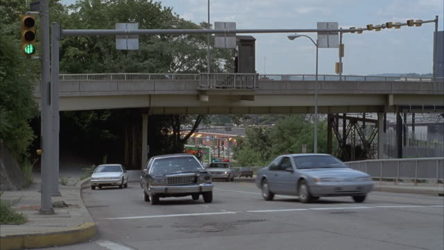 tracking shot of blue ford crown victoria driving towards frame on road beneath overpass. - chasing stock videos and b-roll footage