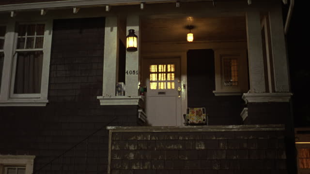 vídeos de stock e filmes b-roll de medium angle of illuminated two car garage. pan left to two story tudor or shingle style house with gray wooden siding and white trim. see address read 4051. - tudor