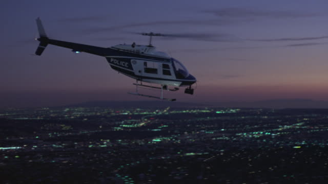 aerial tracking shot of police helicopter flying right, above blocks of city of los angeles . pass by office buildings in century city or los angeles. sky has hues of pink and purple along horizon in far background. beauty shot. - century city stock-videos und b-roll-filmmaterial