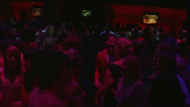 MEDIUM ANGLE OF DISC JOCKEYS PLAYING MUSIC ON TURNTABLES. CAMERA PANS RIGHT TO LEFT AND BACK TO SEE CROWD OF PEOPLE DANCING AND MINGLING ON DANCE FLOOR OF NIGHT CLUB. SEE RED DISCO LIGHTS SHINING OVER CROWD.