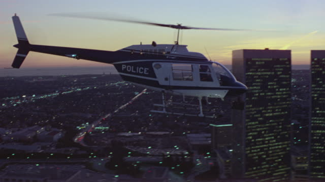 aerial tracking shot of police helicopter flying right, above blocks of city of los angeles . pass by office buildings in century city or los angeles. sky has hues of pink and purple along horizon in far background. neg cut. beauty shot. - century city stock videos & royalty-free footage