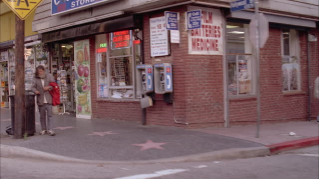 MEDIUM ANGLE MOVING POV OF CITY STREET OR HOLLYWOOD BLVD AND HOLLYWOOD WALK OF FAME. SEE WALK OF FAME STARS IN SIDEWALK. SEE STOREFRONTS AND PEDESTRIANS. SEE HOMELESS MAN ON CORNER.
