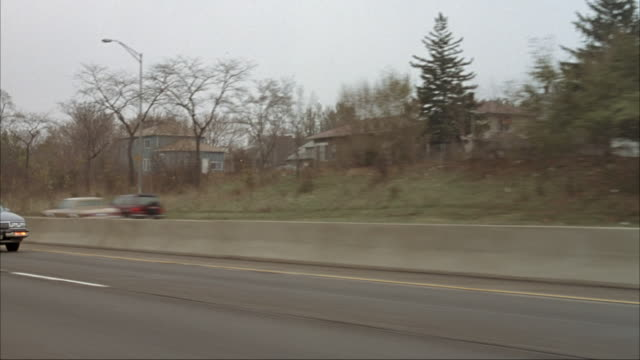 process plate of car driving down freeway. pov is from side windows. see passing cars, overpasses and signs. see houses and townhouses in residential area on sides of freeway. see bare trees and overcast sky. - chicago illinois stock-videos und b-roll-filmmaterial