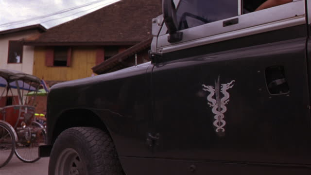medium angle of military vehicle or jeep with insignia of intertwined dragons. resembles caduceus. pedicab seen. as jeep drives away, men, women and children with water guns and two story asian hut style building are seen. - hermesstab stock-videos und b-roll-filmmaterial