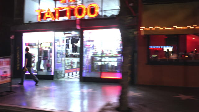 process plate straight right side of hollywood blvd. pass bed behavior adult store, shops, tattoo parlor, restaurants, and clothing stores. hollywood walk of fame visible. pass cars driving and people walking. - tattoo stock videos and b-roll footage