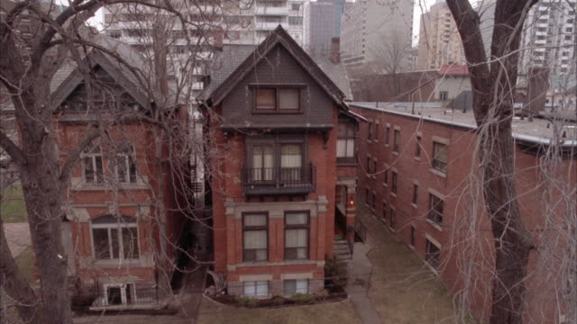 HIGH ANGLE DOWN OF TWO ROW HOUSES OR TOWNHOUSES SIDE BY SIDE. EACH HOUSE IS VERY NARROW AND MAY BE VICTORIAN STYLE.