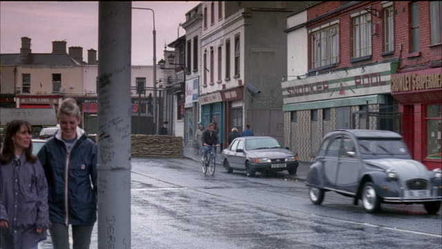 medium angle of small town street. building on right reads snooker pool. very old, gray classic car drives and exits right, green car enters from left and drives into frame. - 1997 stock videos and b-roll footage