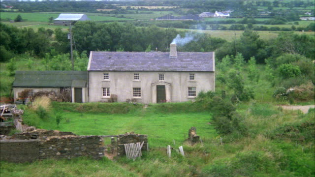 MEDIUM ANGLE OF TWO STORY MASONRY HOUSE IN THE COUNTRYSIDE. HOUSE IS GRAY WITH ONE CHIMNEY AND A WING OR ADDITION ON THE LEFT.  HOUSE MAY DATE FROM 16TH, 17TH, OR 18TH CENTURY.