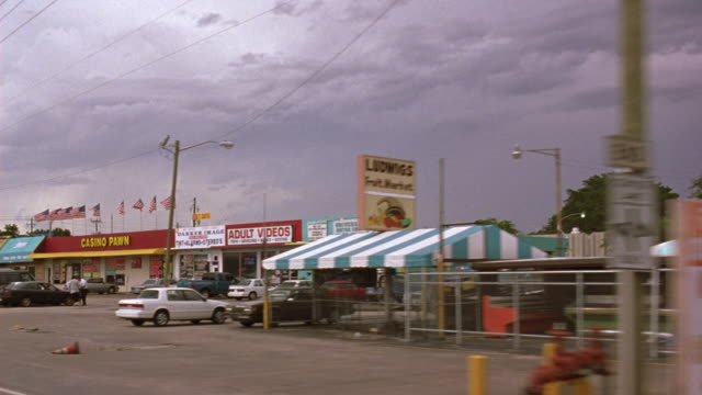 vidéos et rushes de medium angle driving pov of small shops. see delaware chicken farm & seafood market , ludwig's market, casino pawn, tires signs above shops. shot ends on gas station at end of street. - station service