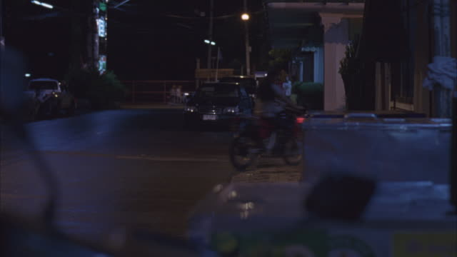 medium angle of dirt bike or motorcycle rider driving bike through city street. see cars parked on both sides of street, city lights in background as biker exits through alley frame right. see traffic and man on sidewalk in background. - motorcycle racing stock videos and b-roll footage