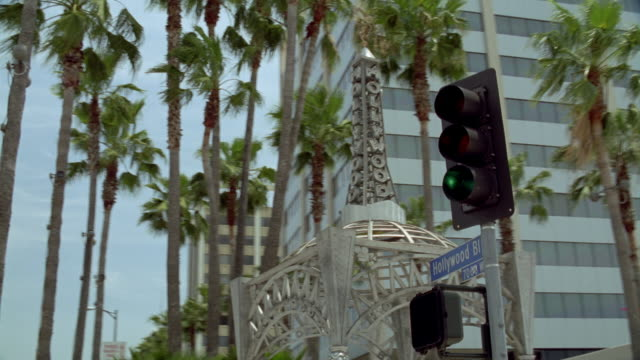 medium angle moving pov of metal gazebo with four naked women as posts and spire on top with hollywood written. see palm trees in background. - hollywood california stock videos & royalty-free footage