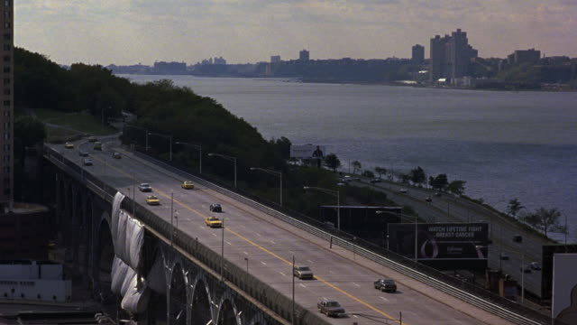 WIDE ANGLE OF FOUR LANE TWO WAY FREEWAY OR HIGHWAY AT BRIDGE OR OVERPASS. COULD BE RIVERSIDE DRIVE IN UPPER WEST SIDE MANHATTAN. SEE RIVER IN BACKGROUND.