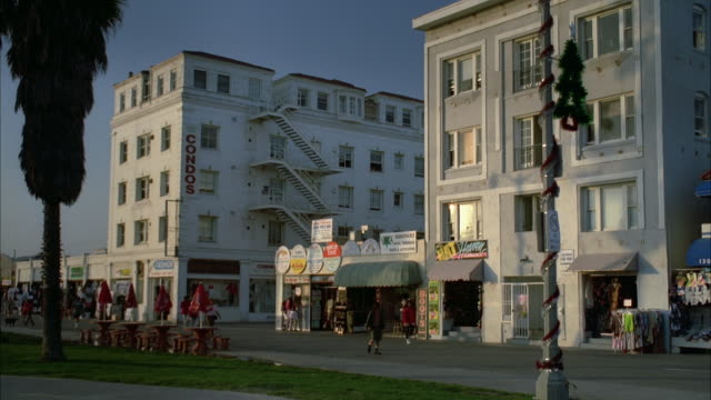 medium angle of venice beach boardwalk. see five story white condominium with fire escape above storefronts. see grey four story apartment building on right above storefronts. - 1989 stock videos and b-roll footage