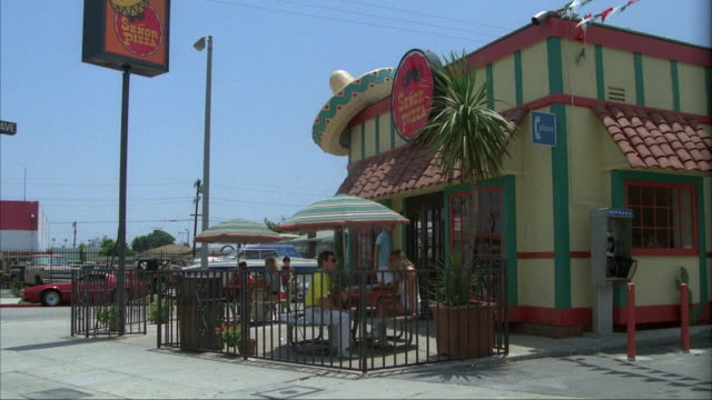MEDIUM ANGLE OF STREET CORNER WITH FAST FOOD RESTAURANT OR PIZZERIA NAMED SENOR PIZZA. PEOPLE OUTSIDE ON PATIO, EATING, PEDESTRIAN AND ROLLER SKATERS PASS BY.