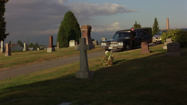 medium angle of path through cemetery. see man in black suit standing in front of black hearse followed by trail of passenger cars stopped at top of small hill. - funeral procession stock videos & royalty-free footage
