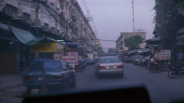medium angle of pov inside a car driving down a busy, rundown city street lined with small shops, parked motorcycles, parked cars, multi-story buildings, and various people. - bangkok stock-videos und b-roll-filmmaterial
