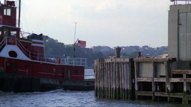 medium angle of hudson river facing new jersey in background. boat dock and building in foreground. red tugboat with american flag pulls barge with junk or garbage, appears from right and moves across to left. - barge stock videos & royalty-free footage