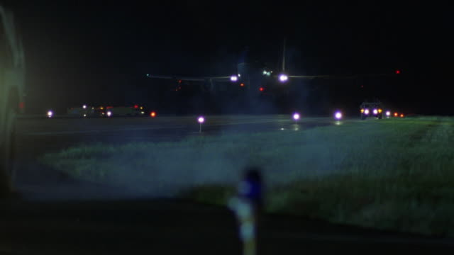 MEDIUM ANGLE OF RUNWAY AT AIRPORT OR AIR FORCE BASE. AIR FORCE ONE AIRPLANE DESCENDS AND LANDS ON RUNWAY. CAMERA PANS LEFT AND AIRPLANE EXITS FRAME TO LEFT.