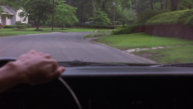 MEDIUM ANGLE FROM INTERIOR OF CAR DRIVING DOWN TWO LANE STREET IN UPPER CLASS RESIDENTIAL NEIGHBORHOOD. SEE LUSH GREEN TREES AND GRASS FLANKING ROAD.