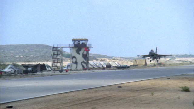 WIDE ANGLE OF MILITARY RUNWAY WITH CAMOUFLAGED CONTROL TOWER IN BACKGROUND. F-16 FIGHTER JET LOWERS TO LAND, PANS LEFT TO FOLLOW JET FLYING ACROSS RUNWAY. PANS BACK TO CONTROL TOWER, SEE SOLDIERS MOVING IN BACKGROUND. MIDDLE EAST.