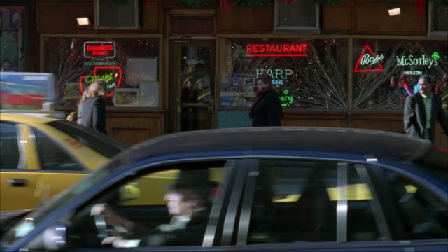 medium angle of restaurant or bar (pj carney's in midtown manhattan). see  city street with taxis traveling left. pedestrians pass by sidewalk in front of bar. man in santa claus costume walks out of restaurant and walks to left. christmas. - 1995 bildbanksvideor och videomaterial från bakom kulisserna