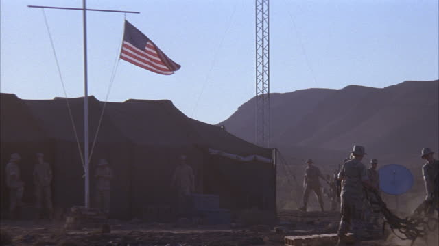 medium angle of american flag in front of tents in desert. could be u.s. military camp or base. see soldiers folding netting. pan right. see satellite dishes and mountains. see military vehicle drive in. see two people exit vehicle. - barracks stock videos & royalty-free footage