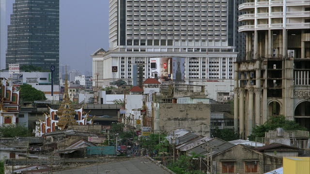 medium angle of city. see rundown area in foreground. see rooftop of temple  and various buildings behind rundown area. see high rise buildings in background. - temple building stock videos & royalty-free footage