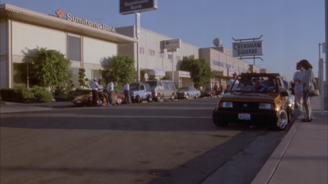 medium angle of city street with cars parked on both sides. building in background has sign that reads sumitomo bank, and another sign in background reads crenshaw square. - inglewood video stock e b–roll