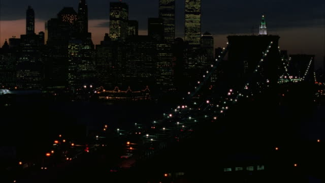wide angle pan left of new york city skyline at dusk. world trade center visible, brooklyn bridge in foreground. pans left, hudson river or body of water in background, sky has tint of purple and red. pans left to skyscrapers, buildings and traffic. - 1989 stock videos and b-roll footage